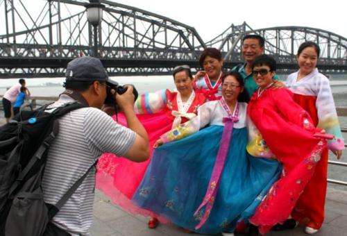 中国游客站在丹东的鸭绿江畔,穿上租来的朝鲜传统服,以鸭绿江断桥和对岸的朝鲜为背景,拍照留念。