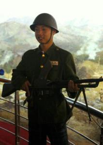 在抗美援朝纪念馆内,游客可装扮成上个世纪朝鲜半岛战争时的军服、扛着假枪,站在一副战争全景图跟前拍照留念。