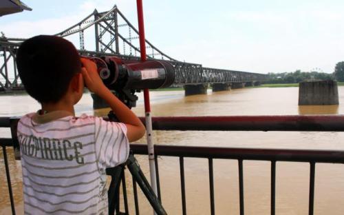 游客站在鸭绿江断桥上,用望远镜窥视对岸的朝鲜。