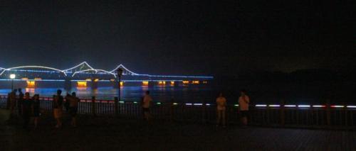 夜晚的鸭绿江畔,中朝友谊桥亮着彩灯,从繁华的丹东延伸至漆黑一片的朝鲜新义州。