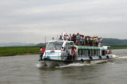 """挤满游人的客船穿梭在朝鲜水域内,这是所谓的""""内河游""""。"""